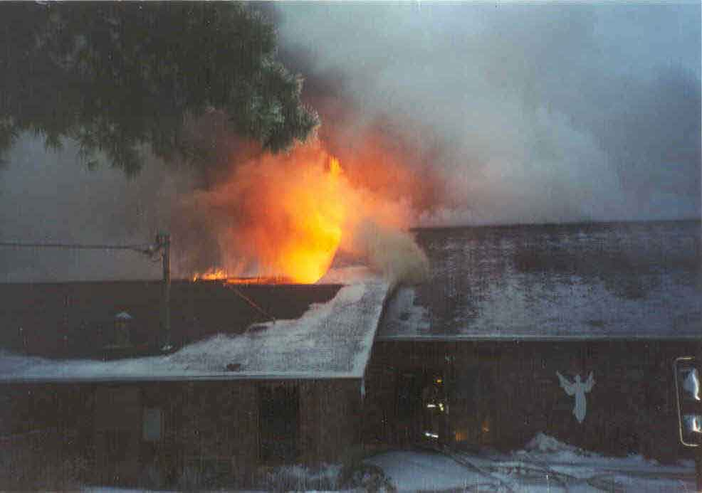 Structure while fully involved, showing doors where crews entered and also showing fire venting over collapsed area of building.