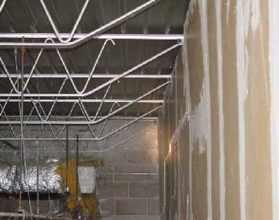 Photo 1. Void space between the corrugated metal roof sheeting and suspended ceiling where the unprotected open-web steel trusses are located.