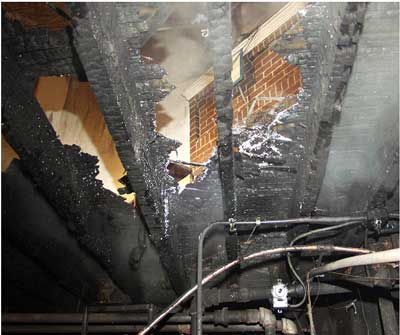 Photo 3. View from basement of floor area consumed by fire
