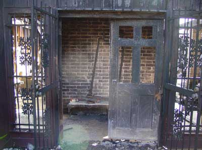 Photo 1. Illustrates the front door (side-A) and the burglar bars restricting entry.