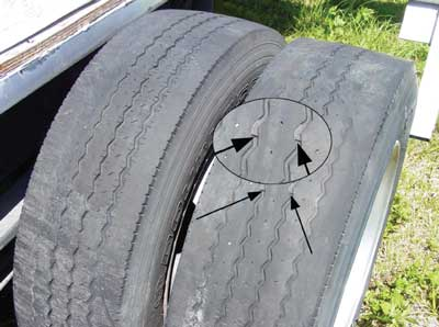 Photo 1. Illustrates the significant wear on one set of the rear tires. Arrows indicate the visible wear bars.