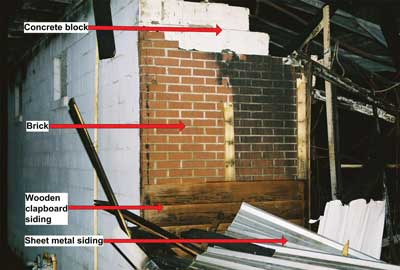 Left front corner of fire building; 4 different layers of construction materials used on front wall can be clearly seen; Collapse area is to right.