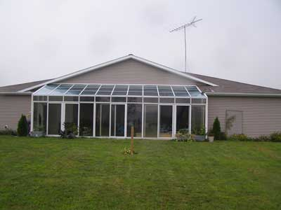 Rear side of the structure with a glass-enclosed porch covering an in-ground pool
