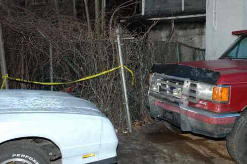 Photograph 2. Hose line stretched 200 feet toward the rear of the structure onto pickup truck and over 6-foot fence.