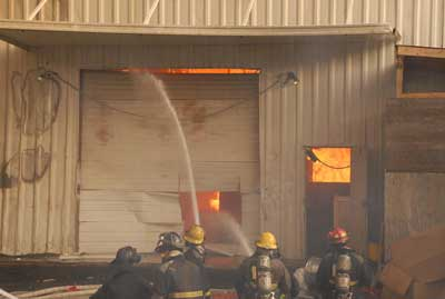 Fire fighters fight the fire from outside the warehouse