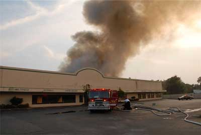 Single fire truck in front of store, with light colored smoke coming from the roof top of the building.