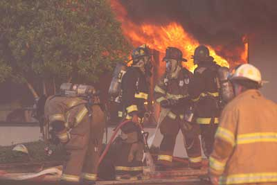 Fire fighters in front of burning building