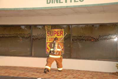 Fire fighter about to break a window of a smoke filled room.