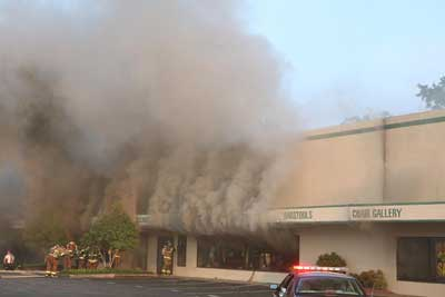 Smoke rolling from the front of the building as the windows are being knocked out.