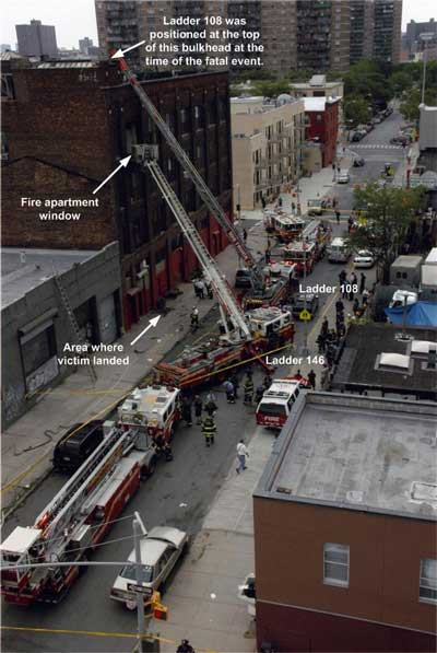 Ladder trucks with ladders extended on the apartment building