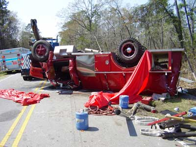 fire truck upside down after rollover in the middle of the road.