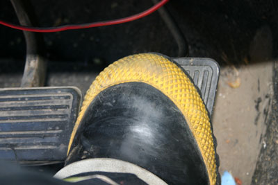 Close up of Boot of Fire Fighter applied to gas pedal and stuck under the brake pedal
