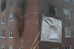 Tarps over a window and smoke rolling from another window.