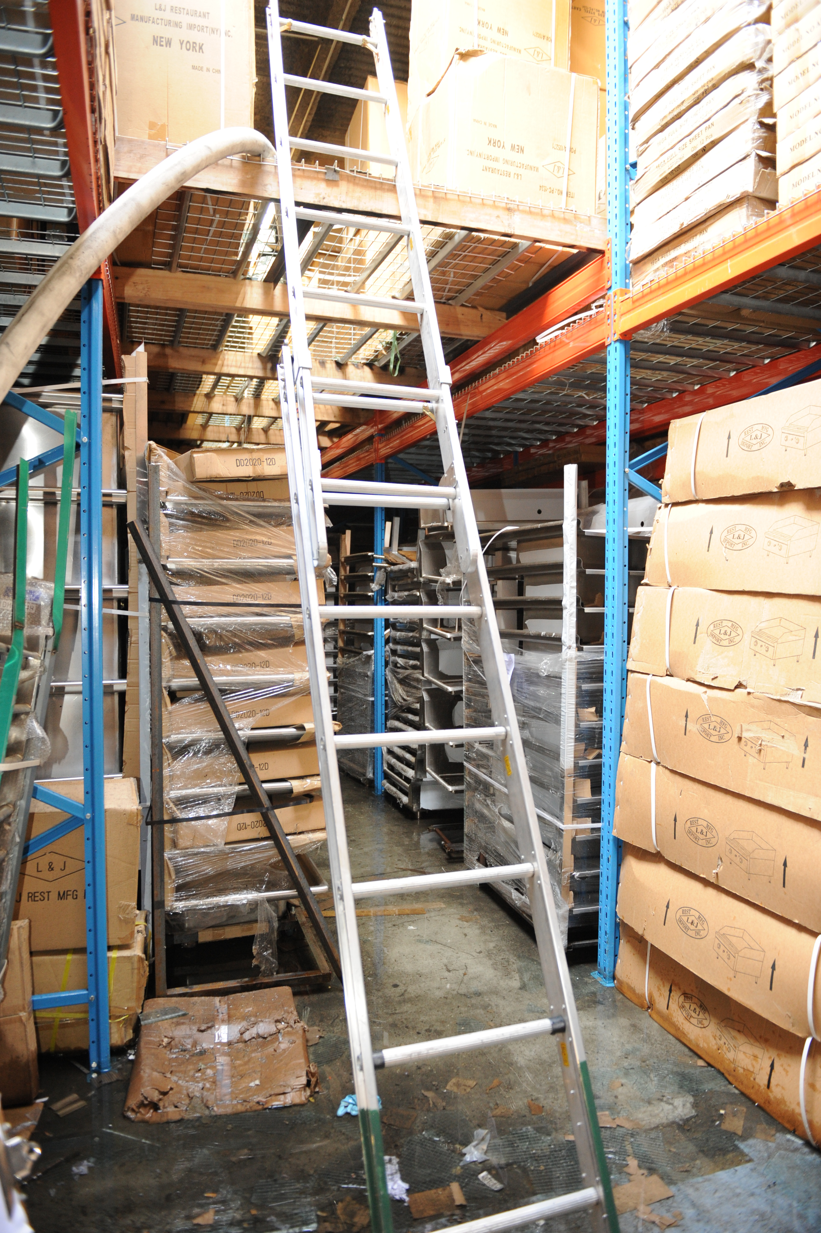 "An extension ladder from the floor of the storage area raised to the ""catwalk"" storage area.  Both storage areas contain large cardboard boxes."