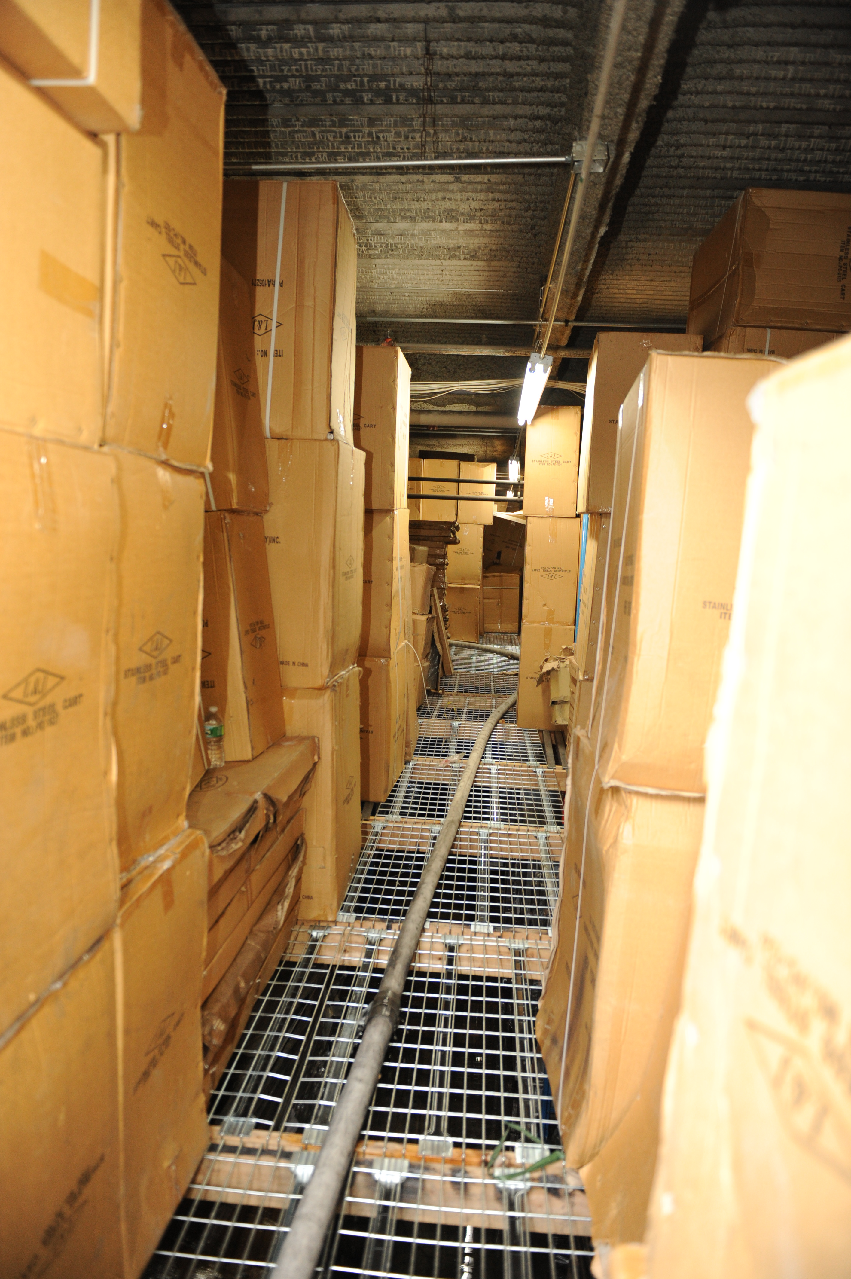 The charged attack hoseline stretched down a narrow aisle of the catwalk storage area. Large cardboard boxes are stacked from floor to ceiling on either side of the aisle.