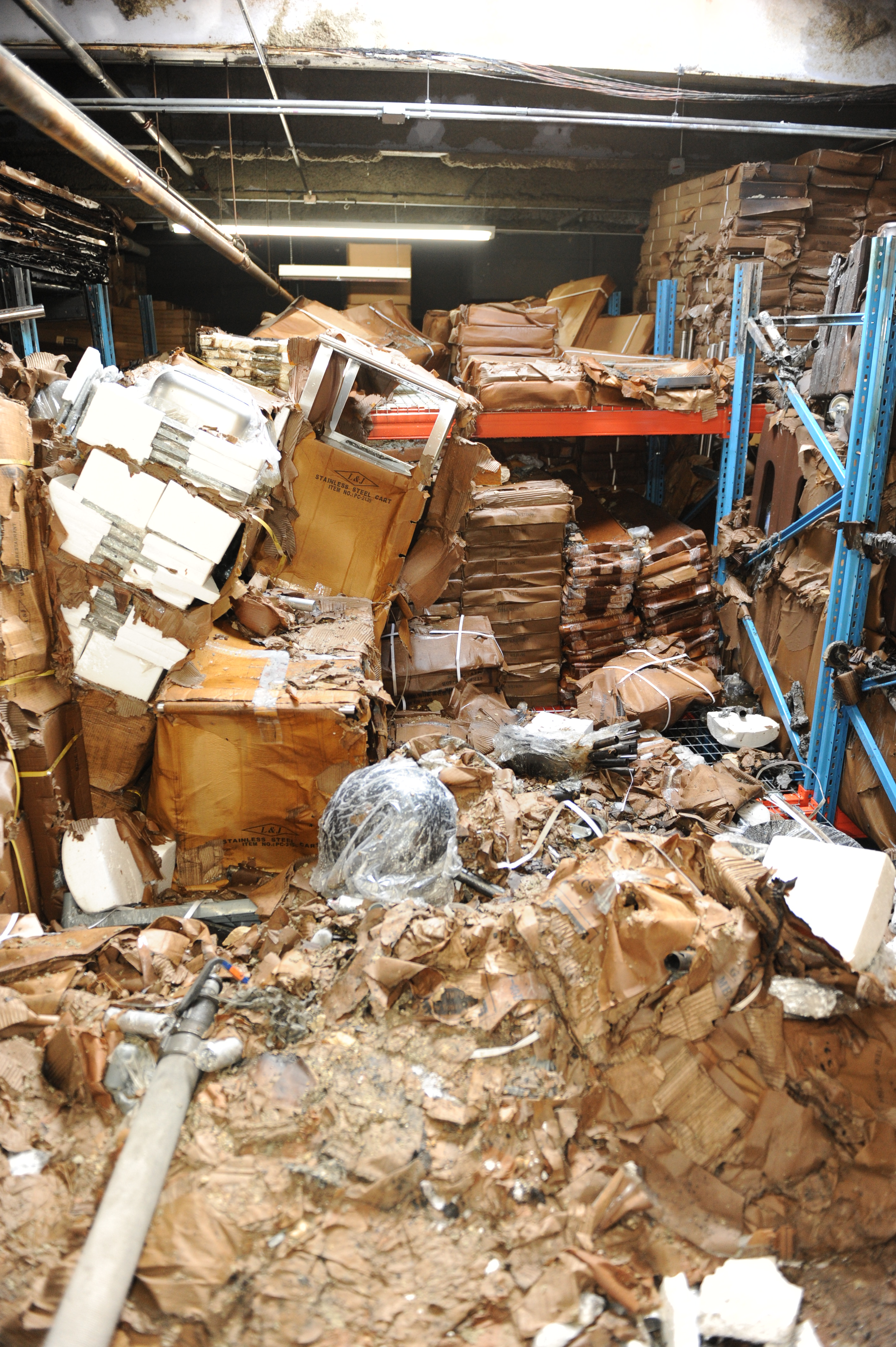 The fire area contains cardboard boxes damage by the fire and water used to suppress the fire.  Many of the cardboard boxes have fallen off the storage racks and broken open revealing plastic shelving and restaurant equipment.