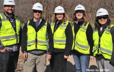 Four NIOSH investigators and one resident rotator take a group photo while wearing hard hats and reflective vests during a site visit in Utah