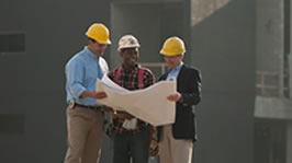 Three contractors wearing hard hats discuss plans outside a building that is being constructed.