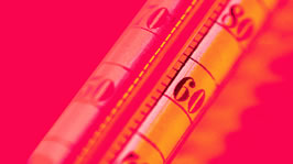 Working in Hot Environments. A close up image of a thermometer with blazing red background