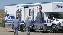 Two miners walk toward the NIOSH mobile screening truck