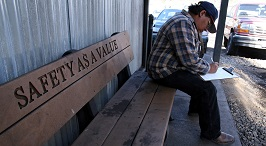 Older worker fills out an application form, while sitting on a bench that has the words Safety as a Value carved into it.