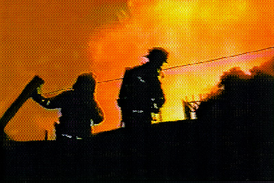 Two firefighters are shown silhouetted against the flame and smoke