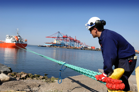 Dock worker secures mooring line to pile.