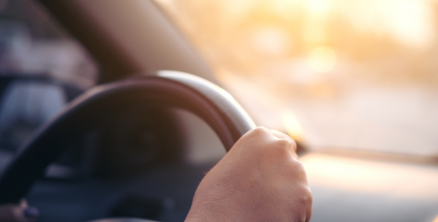 Woman's hand holding on black steering wheel while driving a car during sunset
