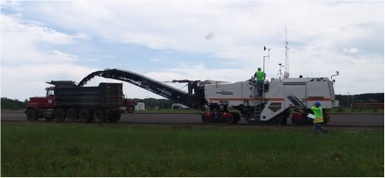 A Wirtgen pavement-milling machine removes the top layer of asphalt from a former airport runway in Marquette, Mich., during controlled field testing of prototype water-spray dust-suppression systems in June 2008, as NIOSH investigator Li-Ming Lo, of DART, walks alongside.  NIOSH wind-measuring equipment and video equipment can be seen mounted on the top of the machine.