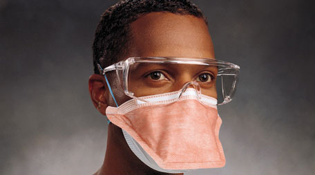 Healthcare worker with filtering facepiece respirator and protective eyewear.