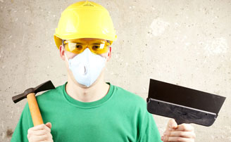 Laborer wearing a helmet, safety glasses, and an N95 filtering facepiece respirator while holding tools in his hands.