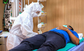 Healthcare worker wearing a protective ensemble with hood, eye protection, and an N95 filtering facepiece respirator. Healthcare worker is leaning over a patient laying on a table.