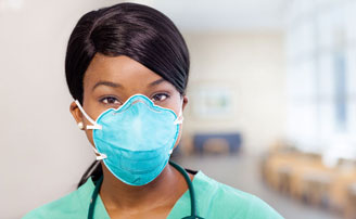 Close up picture of healthcare worker wearing scrub s and an N95 filtering facpiece respirator, looking into the camera.