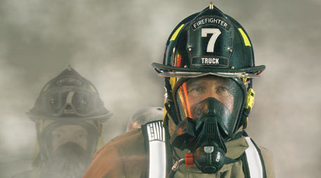 Firefighter wearing personal protective ensemble and self-contained breathing apparatus.