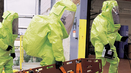 Hazmat technicians entering a building wearing protective ensembles.