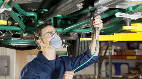 Auto worker wearing filtering facepiece respirator, protective eye wear, and hearing protection.