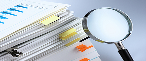 Stack of papers with a magnifying glass suggesting investigation and analysis