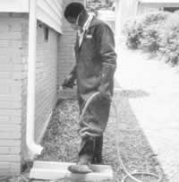 worker spraying termiticide at base of a building under a downspout
