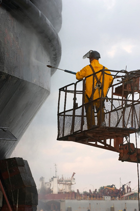 A worker pressure washes a vessel prior to repair