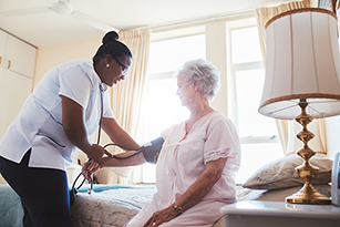 nurse helping older woman