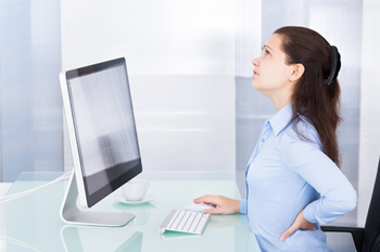 female sitting at computer in an office environment with her hand on the small of her back