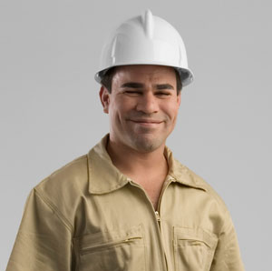 A Hispanic construction worker smiles with satisfaction