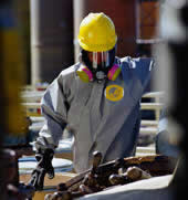 Worker wearing respirator and chemical protective clothing