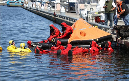 Fishermen in their immersion suits practice life raft entry at Fishermen's Safety Day in Seattle, WA