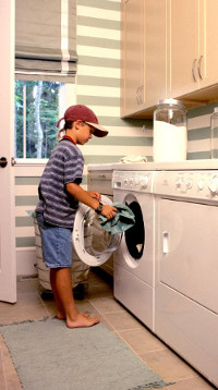 young boy doing laundry at home