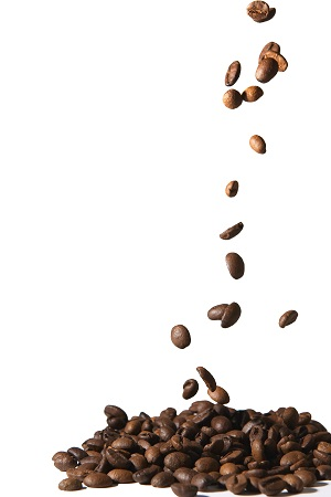 Coffee beans falling into pile isolated on white