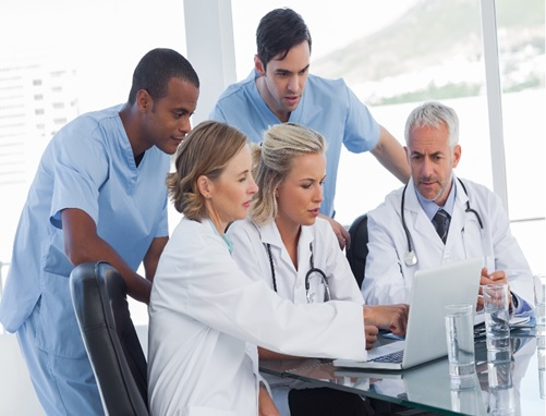 A group of healthcare workers huddle around a laptop computer