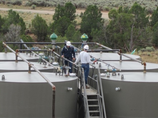 workers inspect oil production tanks