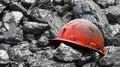 Red hard hat covered with coal dust sitting on pile of coal.