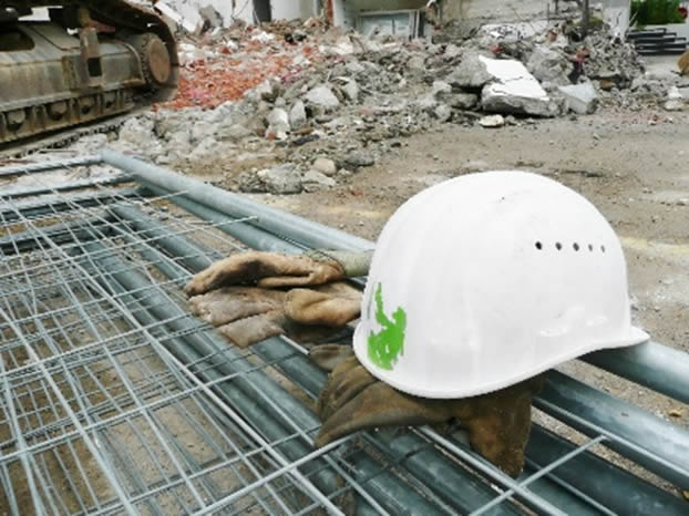 A construction helmet laying on a pair of work gloves